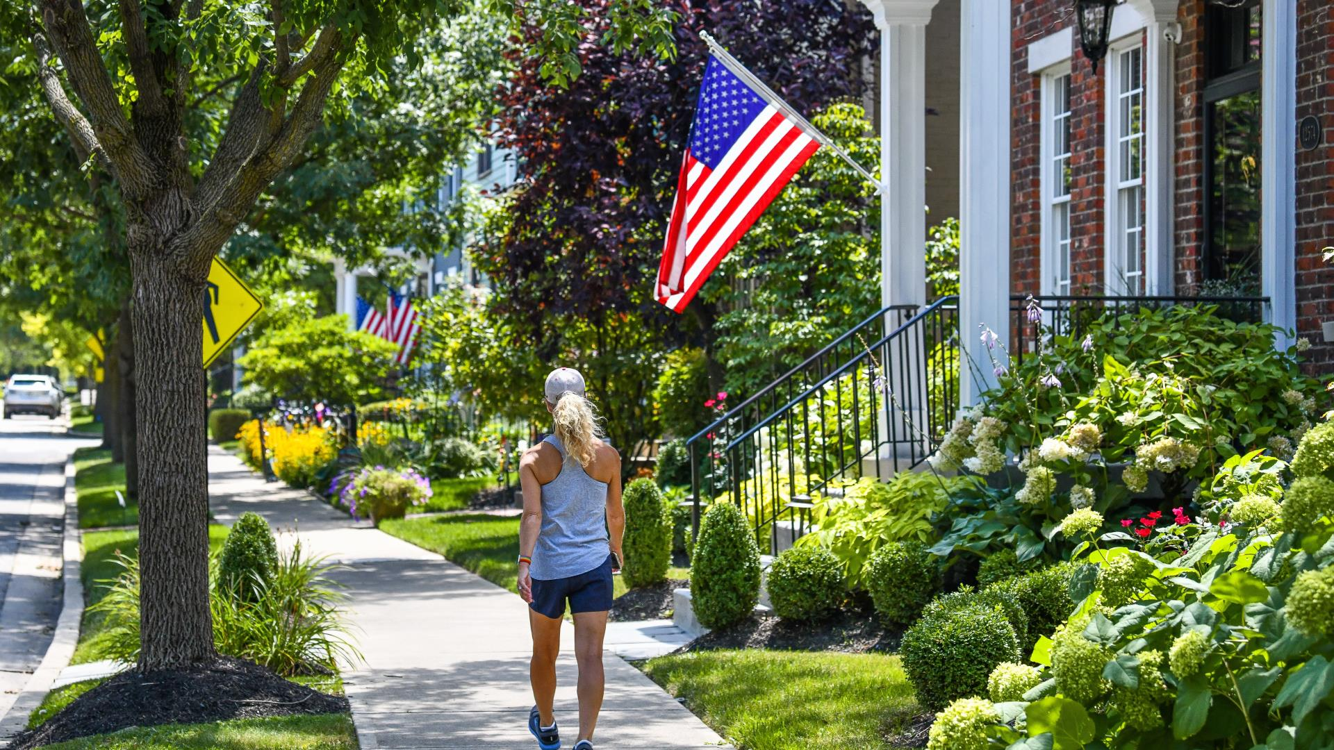 Woman walking on Sidewalk with US Flag